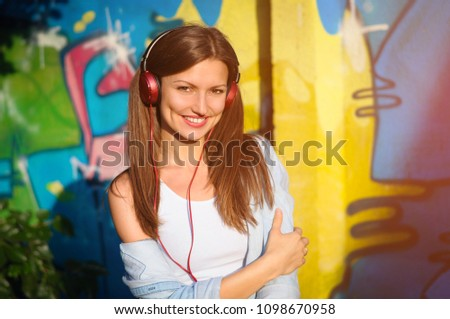 Stock Photo Beautiful woman listening to music on red headphones on graffiti background