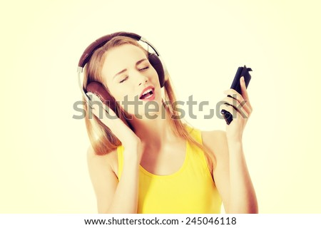 Beautiful woman listening to music with headphones. #245046118