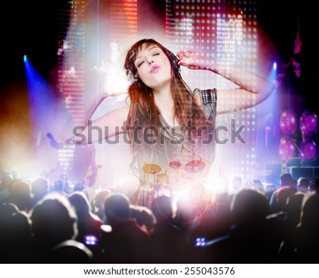 Beautiful woman listening to music with headphones and silhouettes of concert crowd in front of bright stage lights. Concept background of live music and party