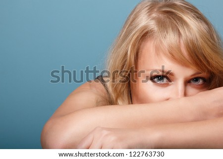 beautiful woman looking at camera, mid adult female face and hands, isolated on blue background