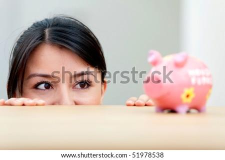 Beautiful woman looking at her savings in a piggybank
