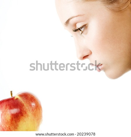 Beautiful woman looking into apple on white background, square composition, shallow DOF.