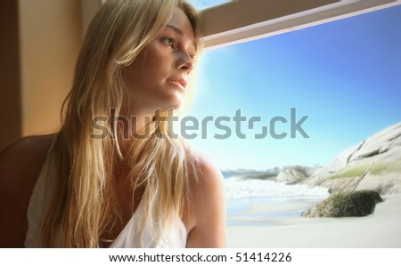 Beautiful woman looking out of a window
