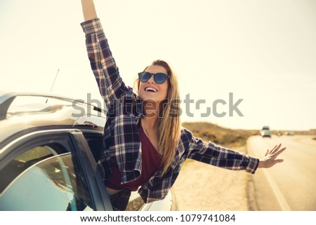 Beautiful woman looking out the car window with open arms enjoying the sunshine