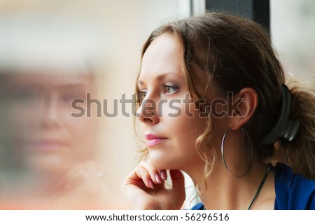 Beautiful woman looking through a window.