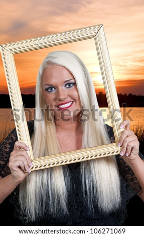 Beautiful woman looking through an ornate picture frame at the beach