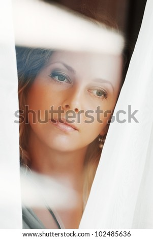 Beautiful woman looking through the window