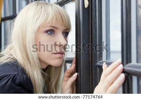 Beautiful woman looking through the window