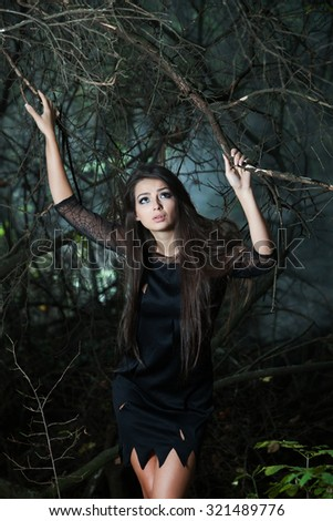 Beautiful woman lost in the wood. Lost girl in forest. Woman lost, sad, disoriented and scared. Brunette woman portrait in forest