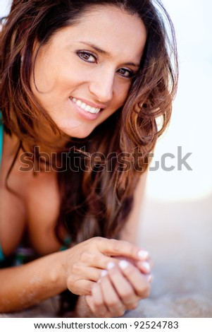 Beautiful woman lying at the beach and smiling