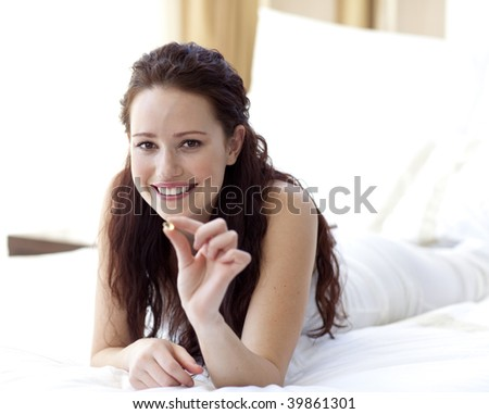 Beautiful woman lying in bed holding a pill