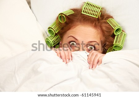 Beautiful woman lying in bed with hair curlers giving an amazed look