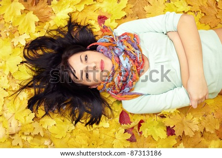 beautiful woman lying in leaves wearing colorful scarf