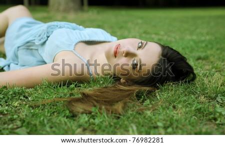 Beautiful woman lying on a green meadow
