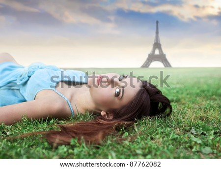 Beautiful woman lying on a green meadow with Eiffel Tower in the background