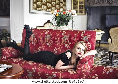 Beautiful woman lying on a sofa in a luxury hotel