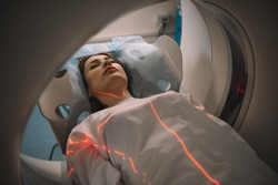 beautiful woman lying on ct scanner bed during tomography test in hospital