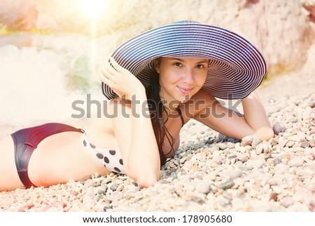 Beautiful woman lying on the beach at summer. Sun beams. Summer sun light, summer colors.