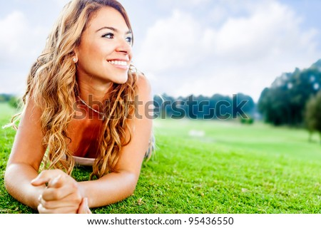 Beautiful woman lying on the floor at the park