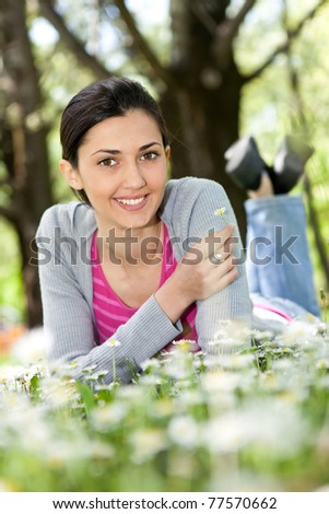 beautiful woman lying on the grass with flowers (focus on girl)