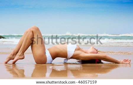beautiful woman lying on the wet sand against ocean and blue sky