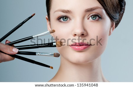 beautiful woman. Makeup brushes.