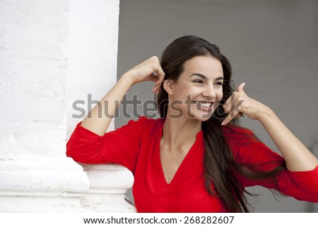 Beautiful woman making a call me gesture, happy girl in red dress on white wall background