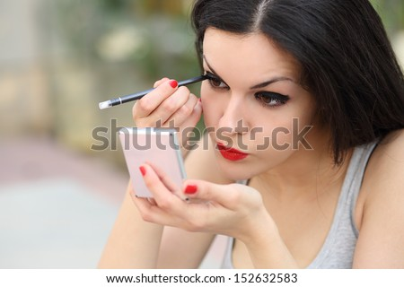 Beautiful woman making up eyelashes herself with a hand mirror outdoor
