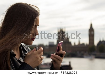 Beautiful woman making up with Big Ben in background