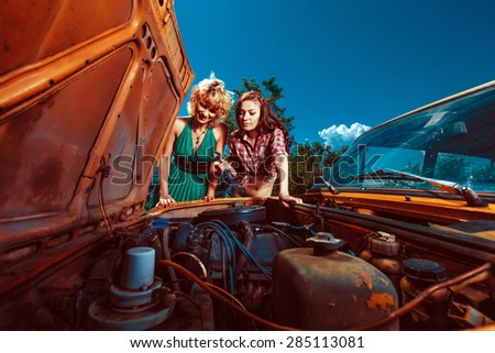 Beautiful woman mechanic is repairing a car another woman is watching.