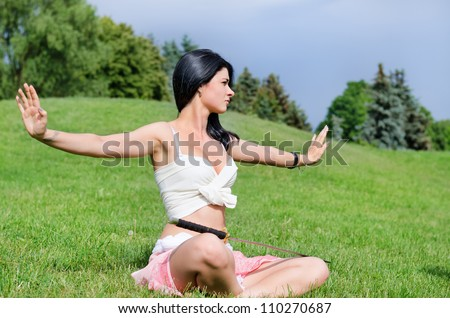 Beautiful woman meditates on green lawn with katana sword  put on feet