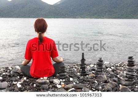 beautiful woman meditation on the stones beach; Thailand