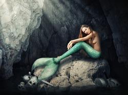 Beautiful woman mermaid sitting on stones  in dark cave. Helmets and skull, broken swords in water