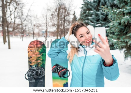 Beautiful woman, mobile phone talking video call, pictures selfie. Sports jumpsuit. Snowboards background snow, Christmas trees. Emotions happiness fun smile enjoyment winter resort. Free space text
