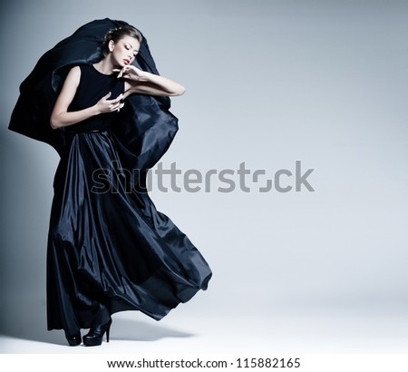 beautiful woman model dressed in an elegant dress in a fashion pose