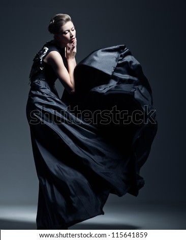 beautiful woman model dressed in an elegant long blueish black dress in a fashion pose