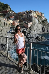 Beautiful woman model in a white t-shirt enjoys the view of the Manarola  Cinque Terre and wave with her hand on the observation deck on a sunny summer day