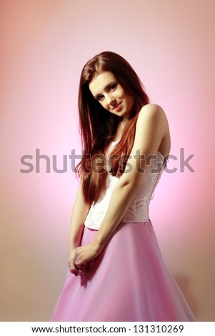 Beautiful woman model portrait in light pink dress on pink background smiling sweet, genuine and happy. Gorgeous dreaming female fashion model brunette.