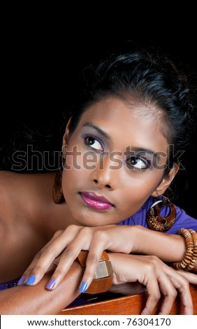 beautiful woman of east indian ancestry looking away from you with chin resting on chair arm