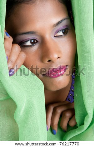 beautiful woman of east indian descent looks from behind a green curtain