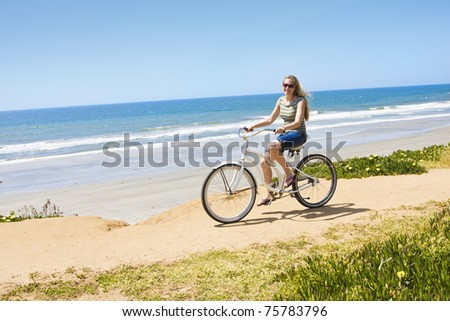 Beautiful Woman on a Bicycle Ride along the beach