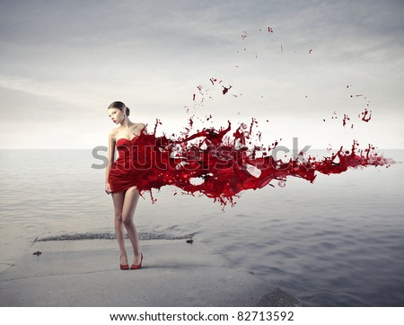Beautiful woman on a pier with her dress melting in red paint