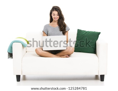 Beautiful woman on a sofa working with a laptop, isolated in white