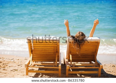 beautiful woman on a tropical beach on a chaise lounge