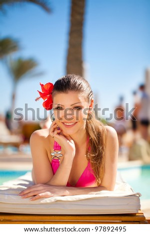 beautiful woman on a tropical beach on a  sun lounger