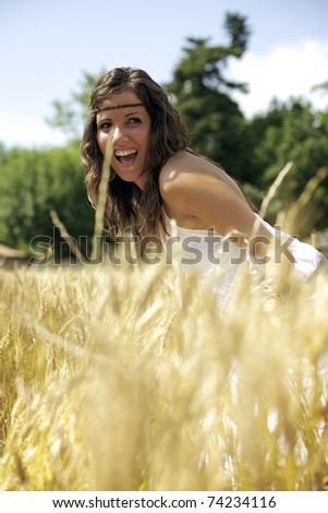 Beautiful woman on a wheat field during a hot summer afternoon. She dresses in white. Color photography full of warm and friendly colors.
