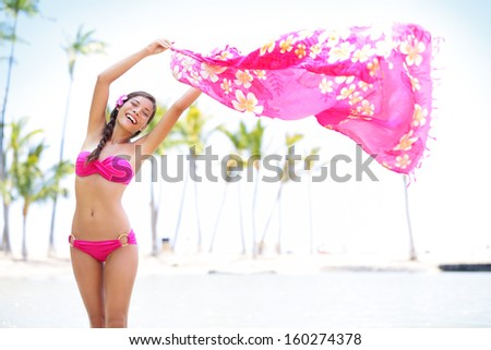 Beautiful woman on beach waving pink scarf in happy bliss on travel vacation. Graceful pretty mixed race young woman in pink bikini on hawaiian beach with palm trees. Big Island, Hawaii, United States