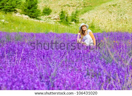 Beautiful woman on lavender meadow, pretty smiling girl sitting on floral field, cute happy female enjoying purple flowers, cheerful teenager relaxed outdoors, natural beauty, summer holiday concept