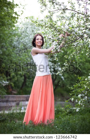 Beautiful woman on the background of a blossoming apple tree