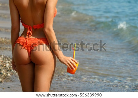 Beautiful woman on the beach with a glass of cocktail